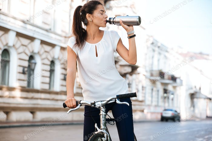 Young woman drinking water from the bottle while riding bicycle