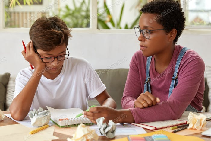 Shot of mixed race guy and female sit together at workplace, discuss ideas for project, wear glasses