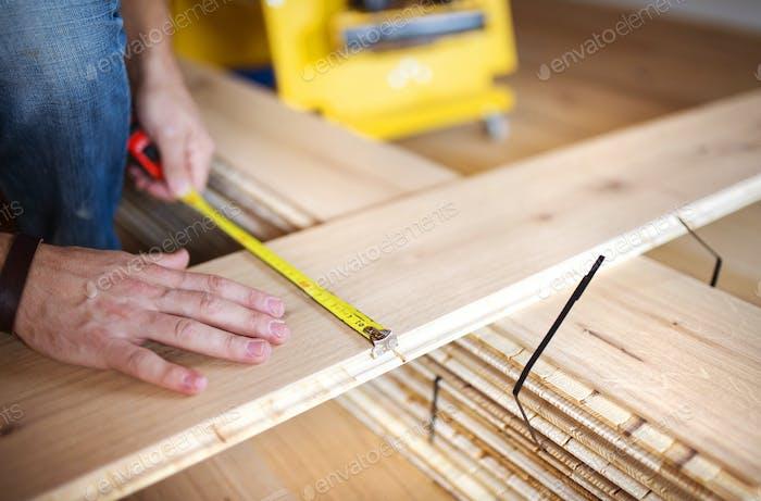 Handyman measuring wooden floor
