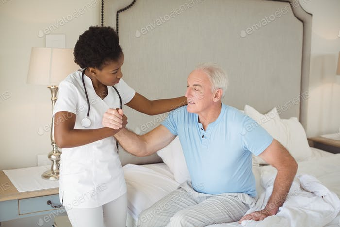 Nurse examining a senior man on bed in bedroom