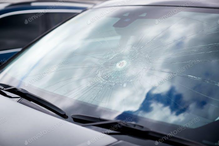 Detalle de daños en el parabrisas del coche destrozado por vandalismo