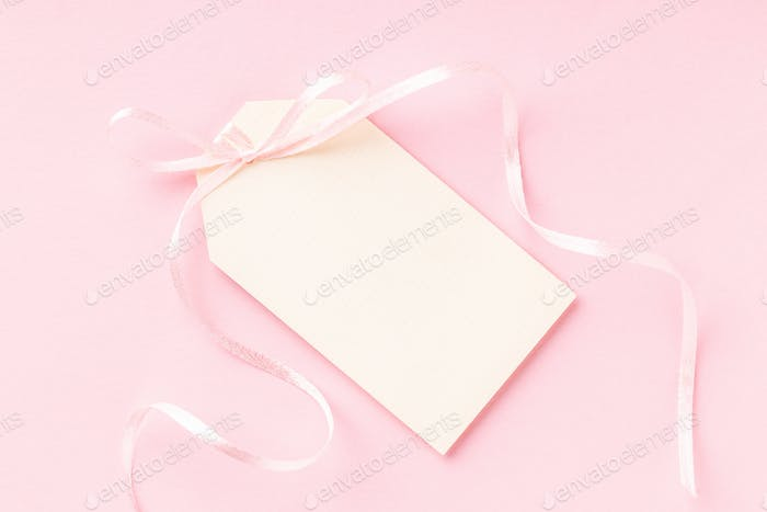 Blank Price Tag with Ribbon on Pink Background.