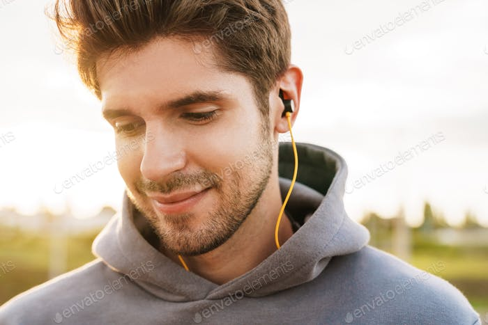 Image closeup of athletic bristle sportsman using earphones and smiling