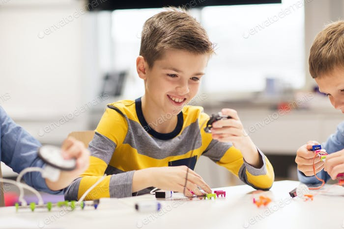 happy boy building robot at robotics school