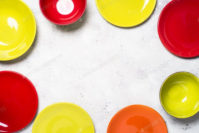 Colored dinnerware - red and green plates on light stone table