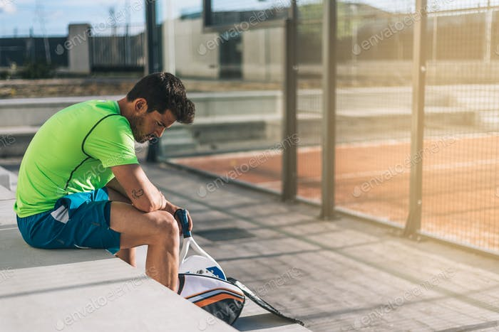Padel player sitting on the floor resting