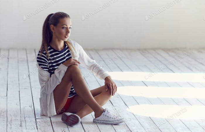 Ein Mädchen, das auf einem Boden sitzt.