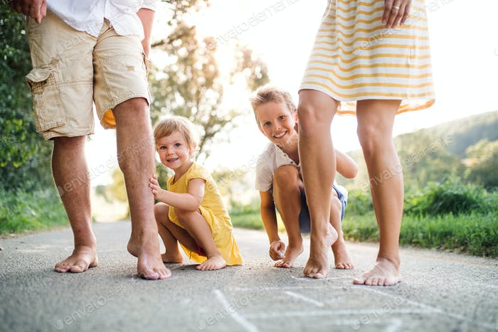 Ein Mittelteil der jungen Familie mit kleinen Kindern, die im Sommer auf einer Straße stehen.