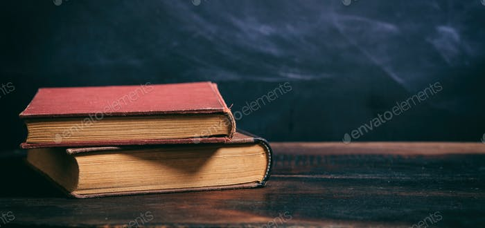 Old books on blackboard background