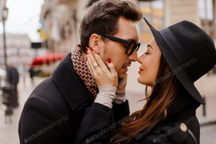 Romantic couple face to face hugging and smiling.