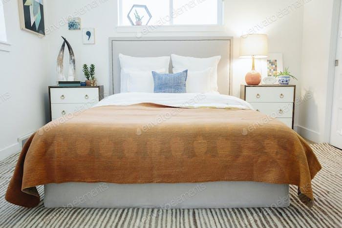 Ein Schlafzimmer in einer Wohnung mit einem Doppelbett und einem gepatchworked Bettbezug.
