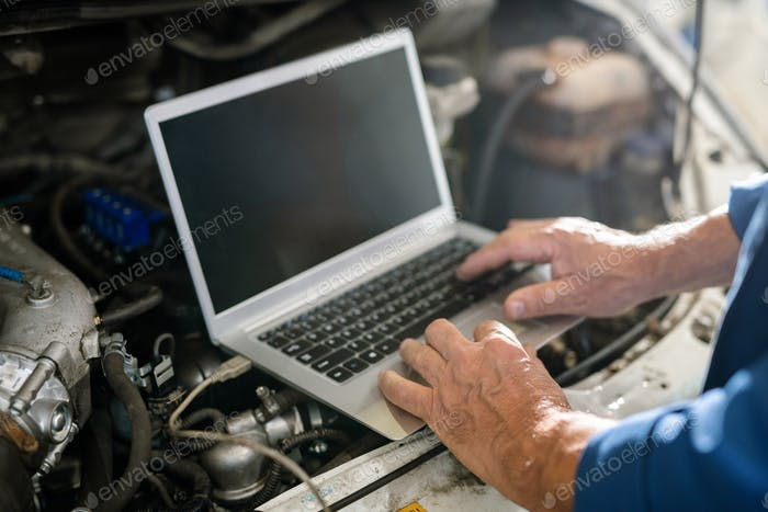 Hands of mature master of car repair service over keyboard of laptop