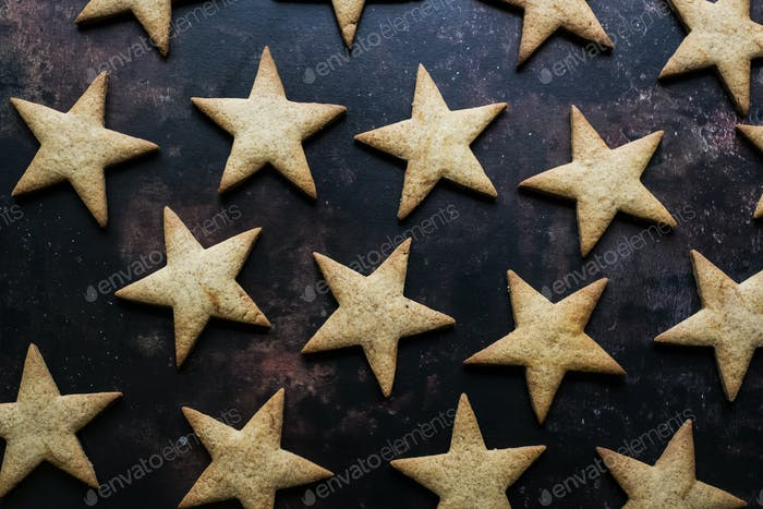 High angle close up of freshly baked star-shaped cookies on black background.