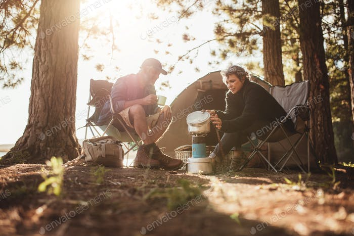 Couple cooking food outdoors on a camping trip