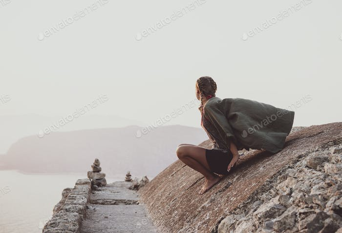 Woman sitting and looking at horizon in Monolithos, Rhodes, Greece