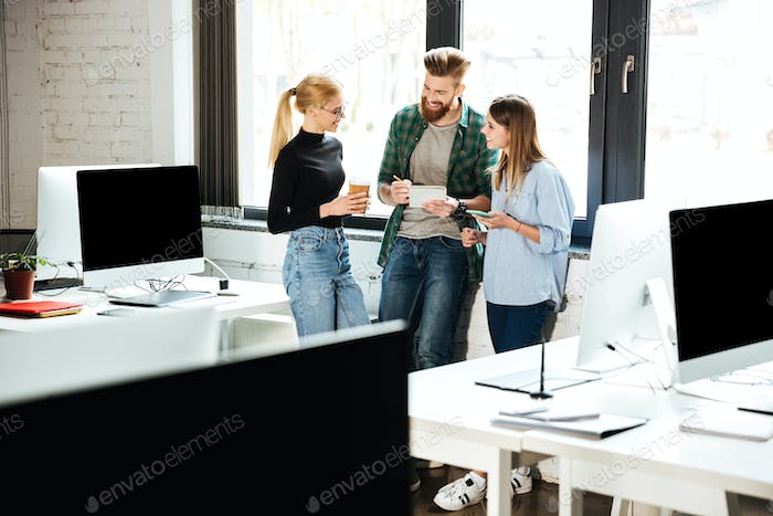 Young concentrated colleagues in office talking with each other