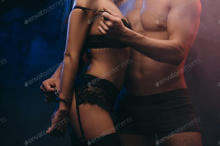 cropped view of sexual couple with handcuffs in smoky room
