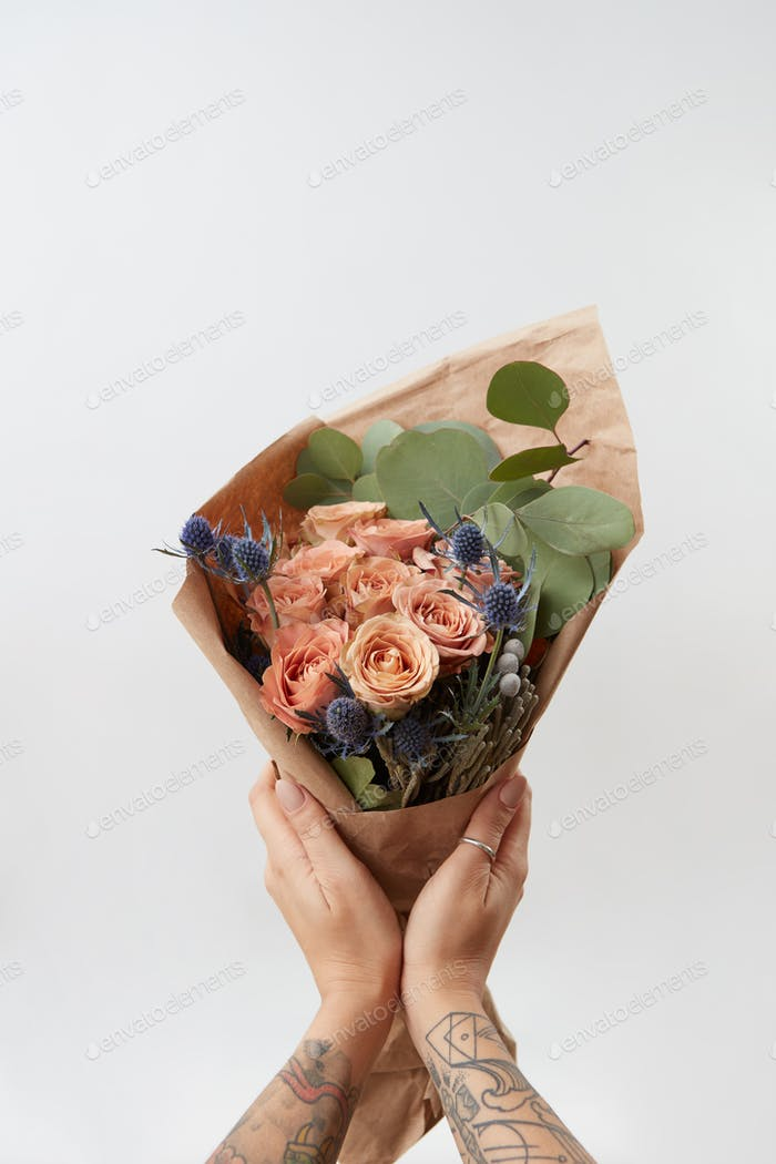 Woman's hands hold colourful blossoming flower bouquet of fresh roses living coral color on a