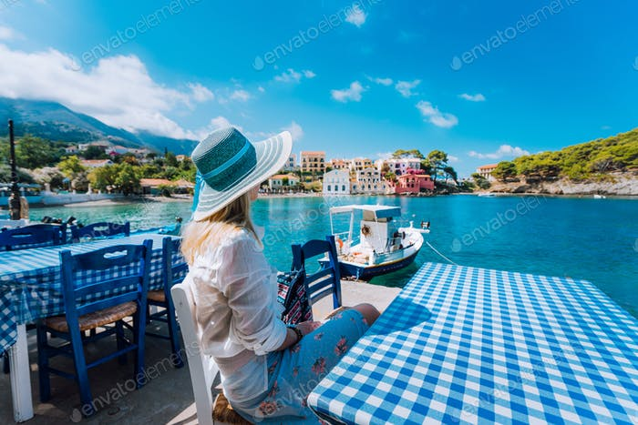 Holiday vacation. Woman in cafe enjoying time in Assos village in front of emerald bay of