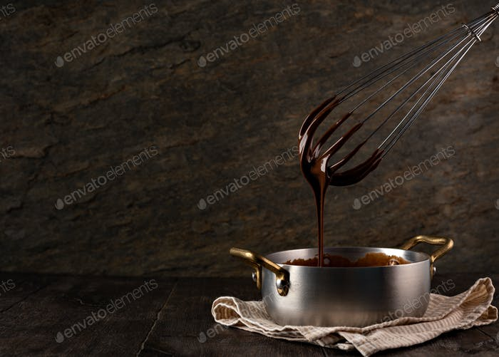 Liquid chocolate cream pouring from a whisk into a ladle.