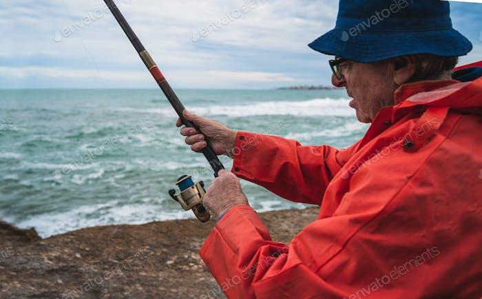 Senior Mann Angeln im Meer.