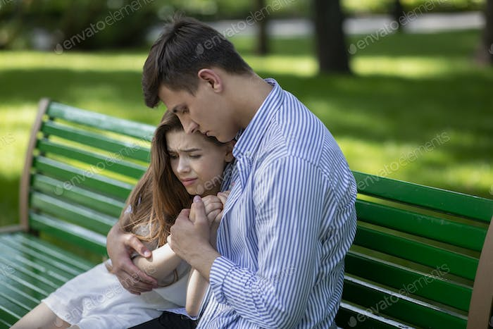 Young guy consoling his upset girlfriend on bench at park