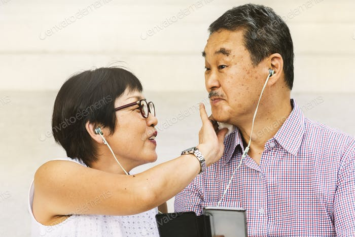 Asian Senior Couple Earphones Concept