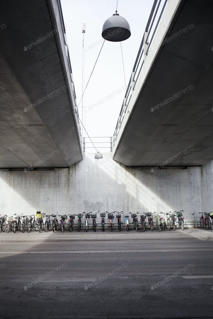 Bicycles parked on sidewalk under bridges