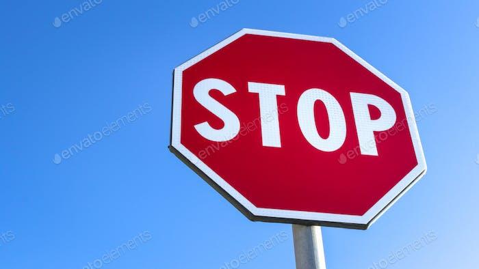 Красный знак остановки и голубое небо