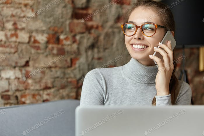 Pretty woman in eyeglasses holding smartphone communicating with shining smile using laptop sitting