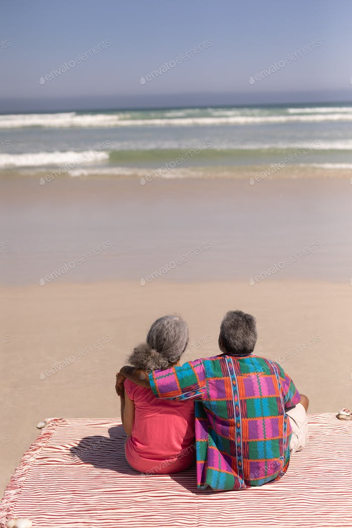Rear view of senior couple sitting on blanket at beach in the sunshine