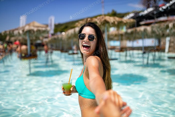 Summer vacation young woman having fun and smiling on the beach in bikini with cocktail