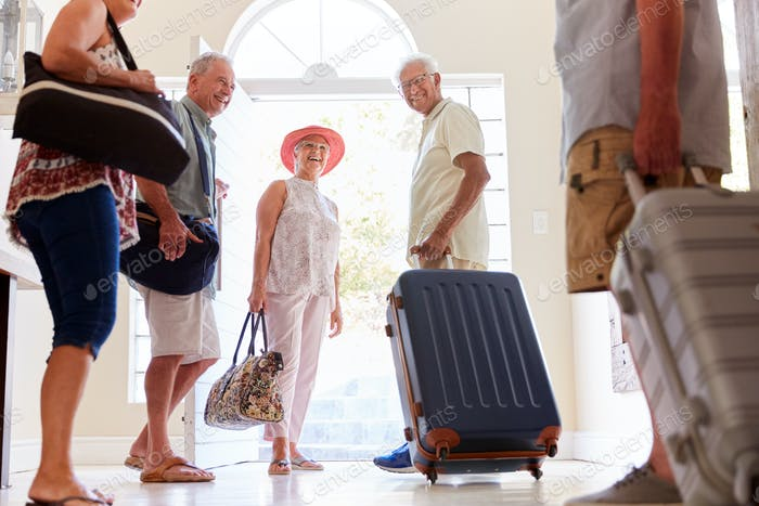 Group Of Senior Friends Standing By Front Door With Luggage About To Leave For Vacation