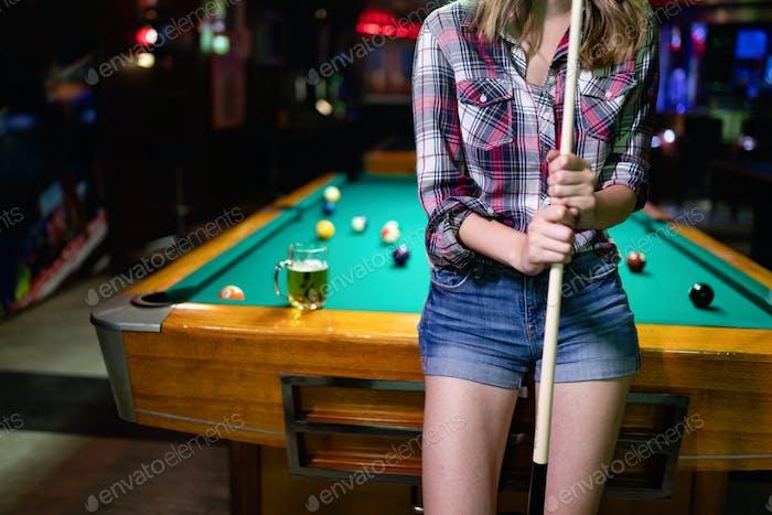 Young beautiful woman having fun and playing billiard in a club