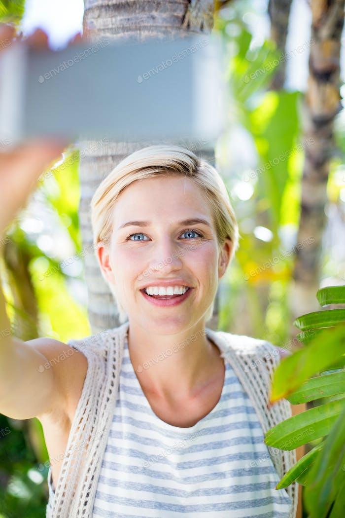 Pretty blonde woman taking selfie in the park