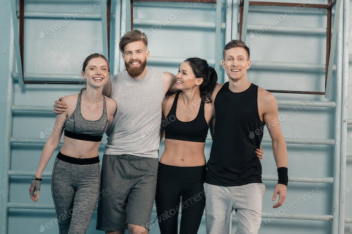 cheerful sporty men and women in gym