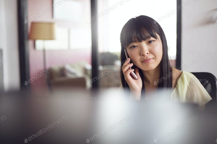 Woman using phone in office