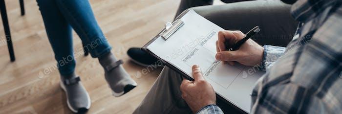 Councelor escribe fortalezas, debilidades, oportunidades en el bloc de notas durante la sesión de terapia