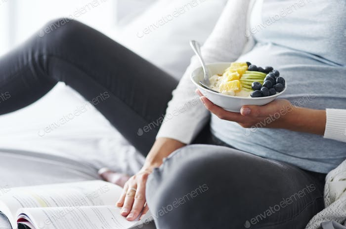Pregnant woman eating and reading a book at bedroom