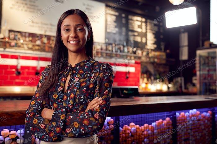 retrato de sonriente mujer bar propietario de pie por contador