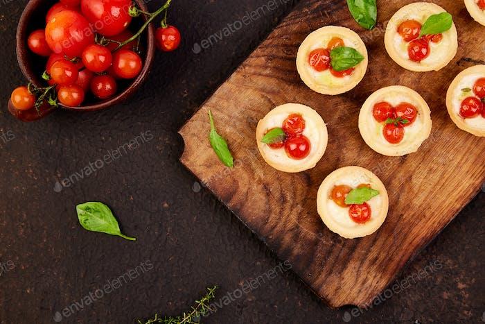 Mini tarts with cherry tomatoes with mozzarella cheese