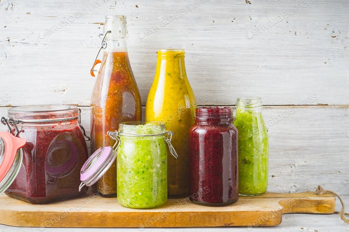 Bottles and jar with different smoothie on the  wooden board horizontal