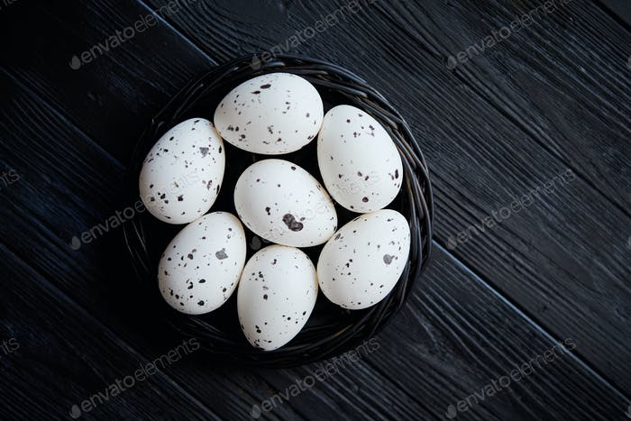 Whole Chicken eggs in a nest on a black rustic wooden background. Easter symbols