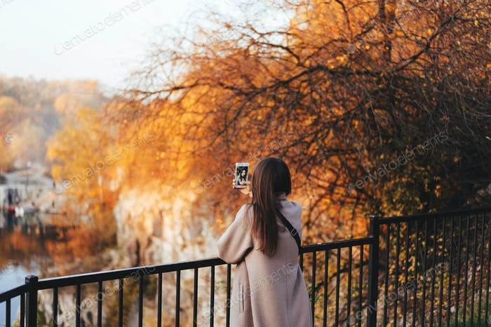 Woman making selfie in the autumn park