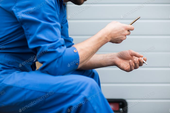 auto mechanic smoking cigarette at car workshop