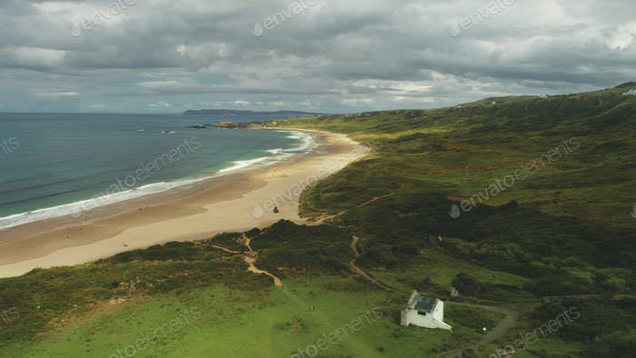 Ocean bay sandy beach aerial panoramic view under gray thick clouds. Green meadows in Irish valleys