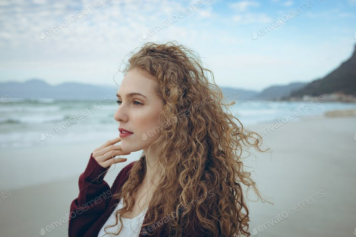 Beautiful young woman with curly hair standing at beach