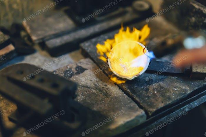 Jeweler melting gold