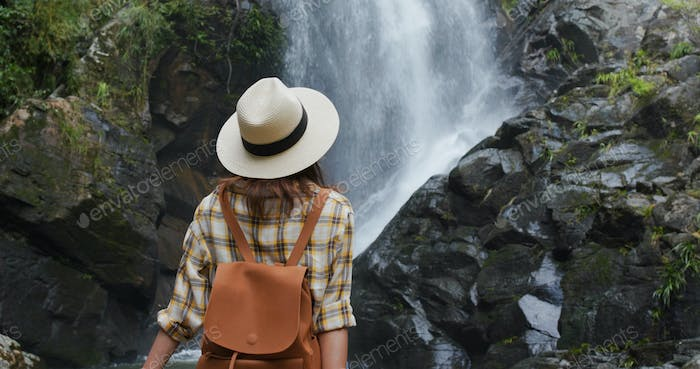 Woman goes hiking and looks at the waterfall in forest