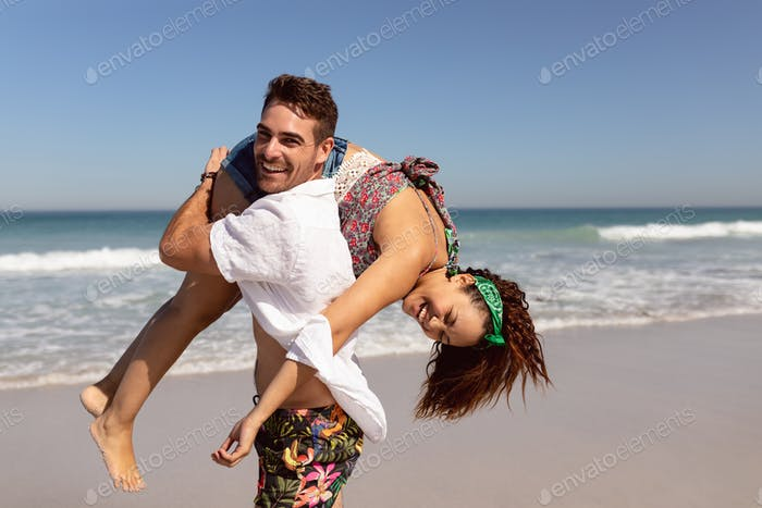 Side view of happy Mixed-race man carrying woman on shoulders on beach in the sunshine